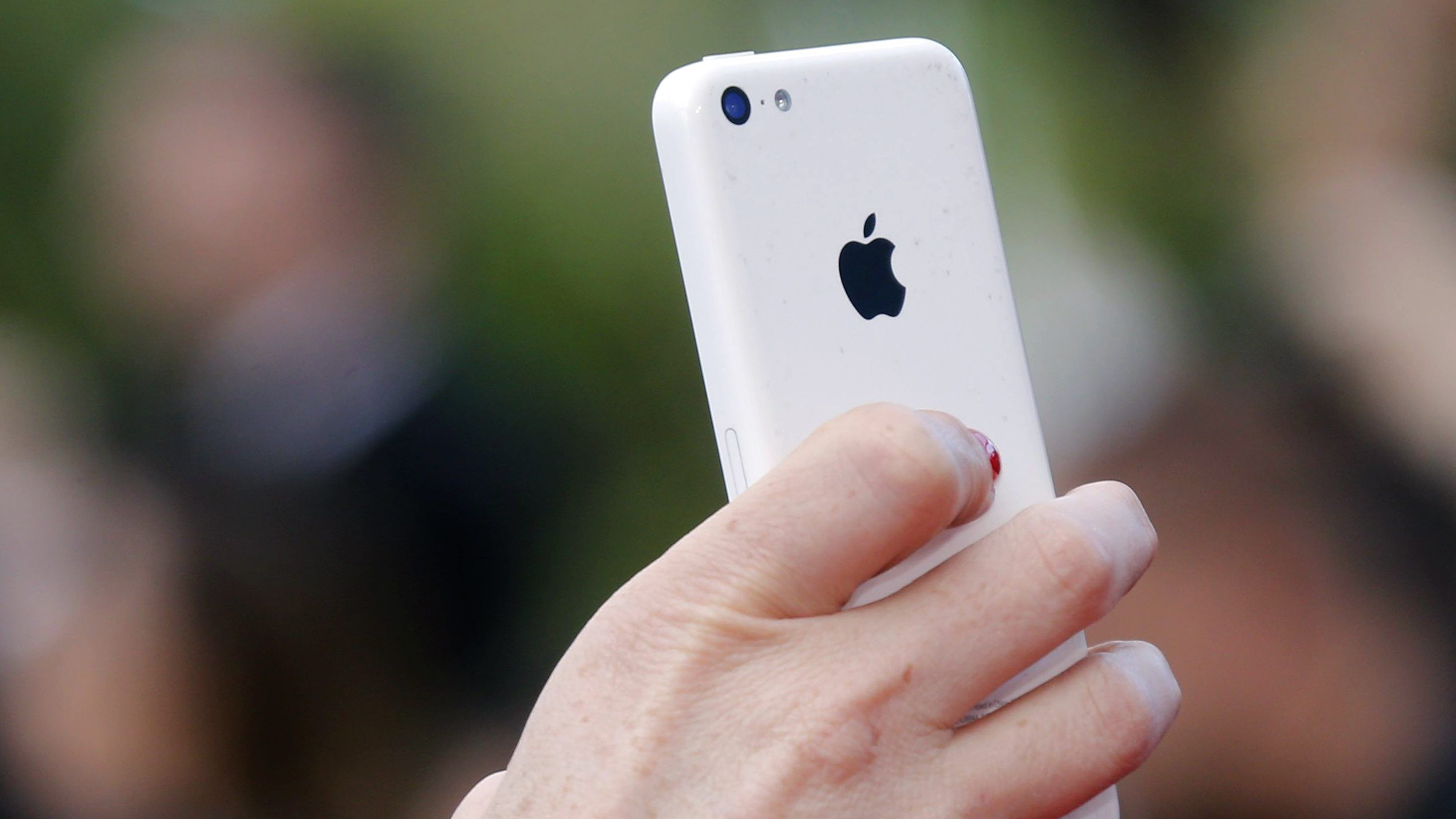 A hand holding a white iPhone