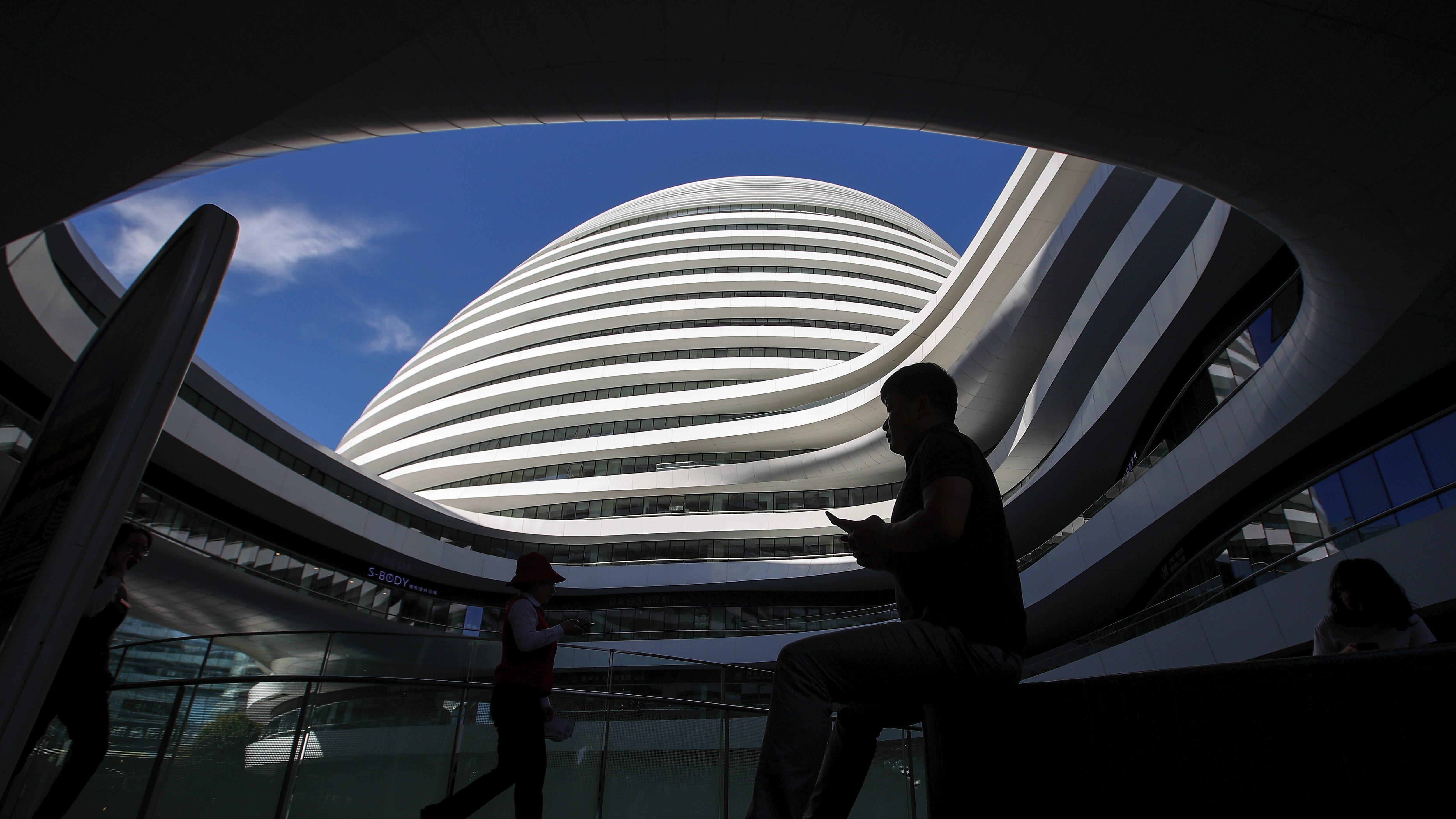 A man sitting near an office building in Beijing.