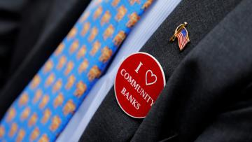 "A person wearing an ""I Love Community Banks"" sticker."