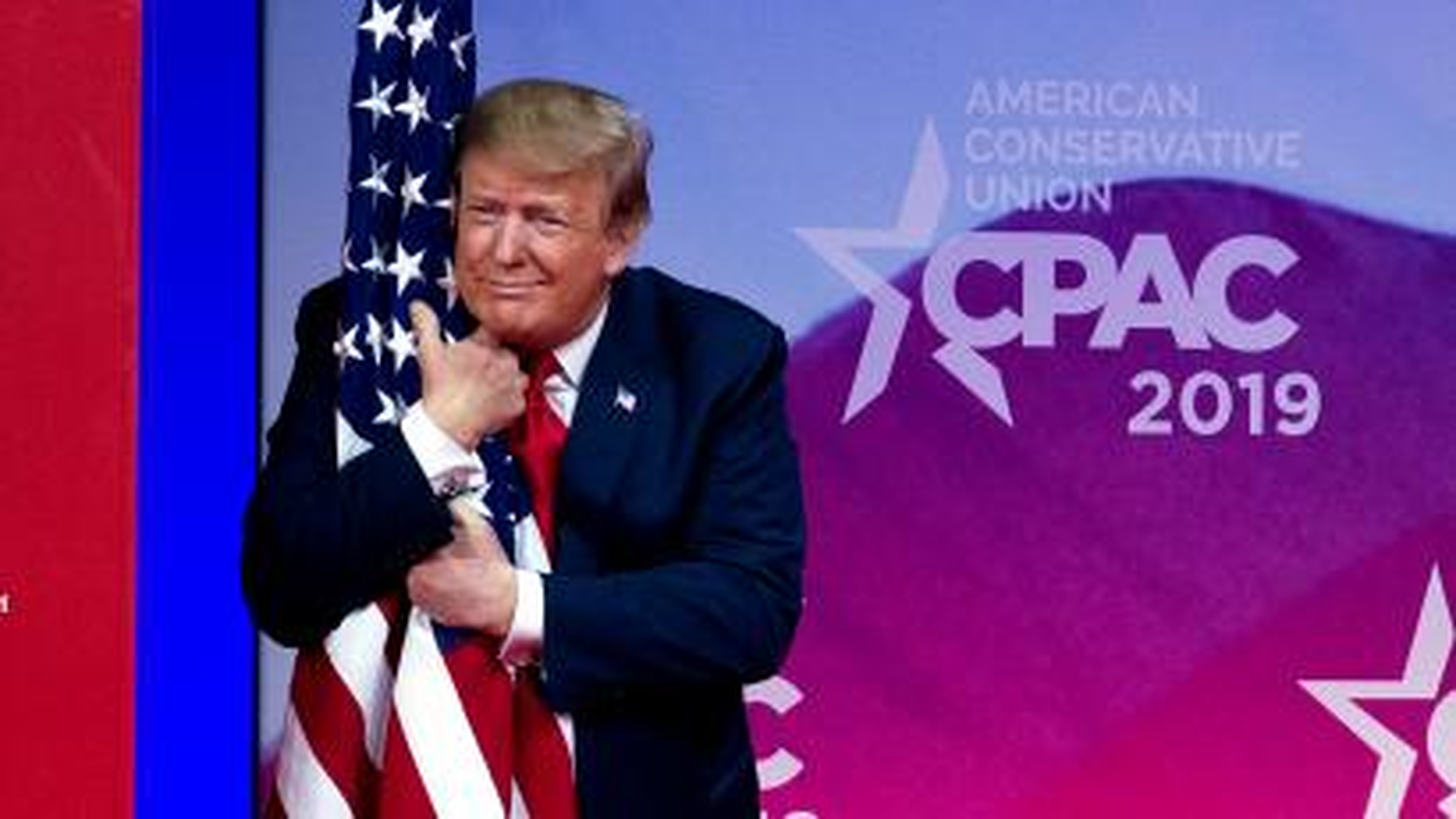 President Donald Trump hugs the American flag