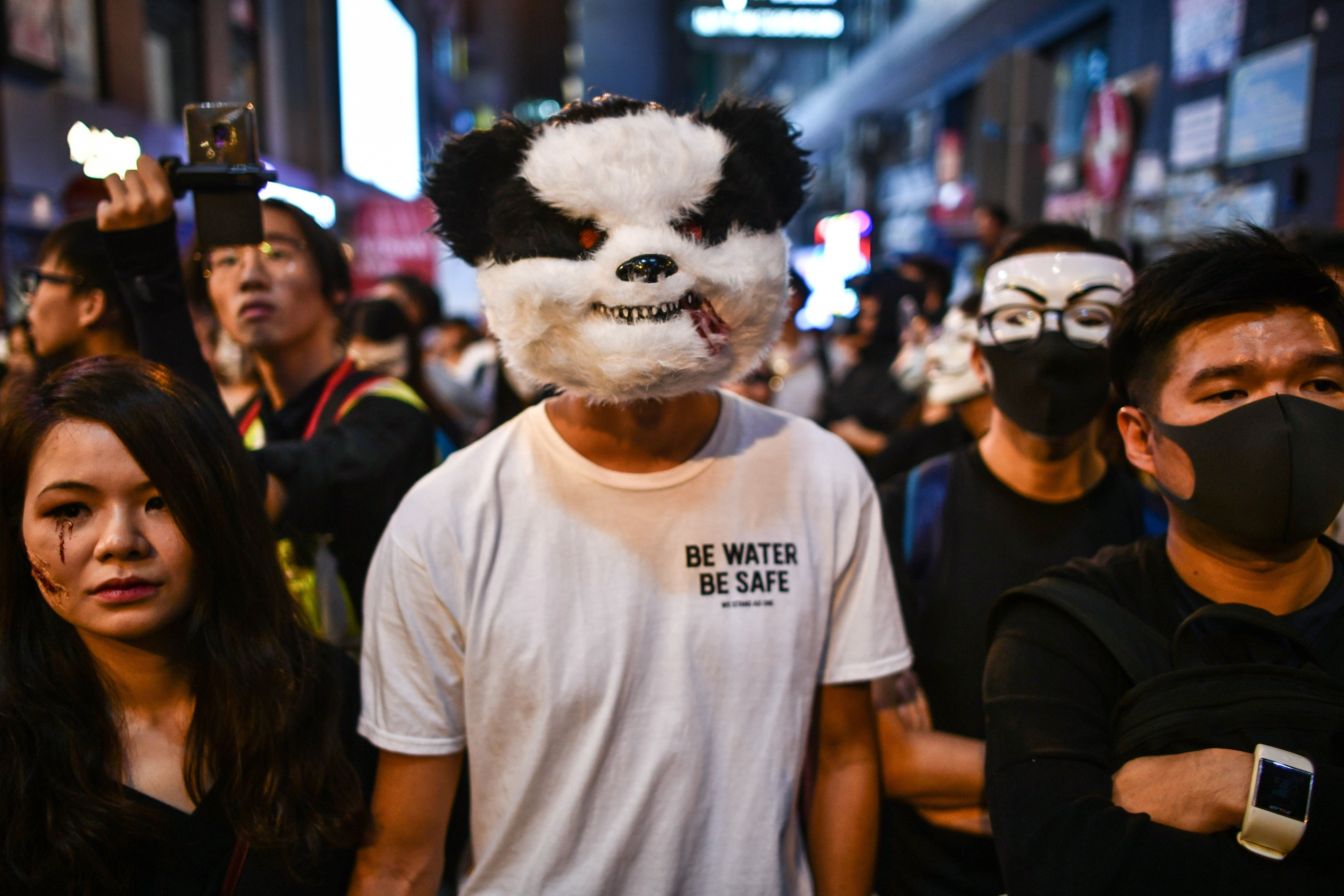 People shout slogans in front of a line of policemen in the Lan Kwai Fong area during Halloween in Hong Kong.