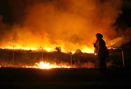 A firefighter monitors the Kincade Fire as it burns through the area on Oct. 24.