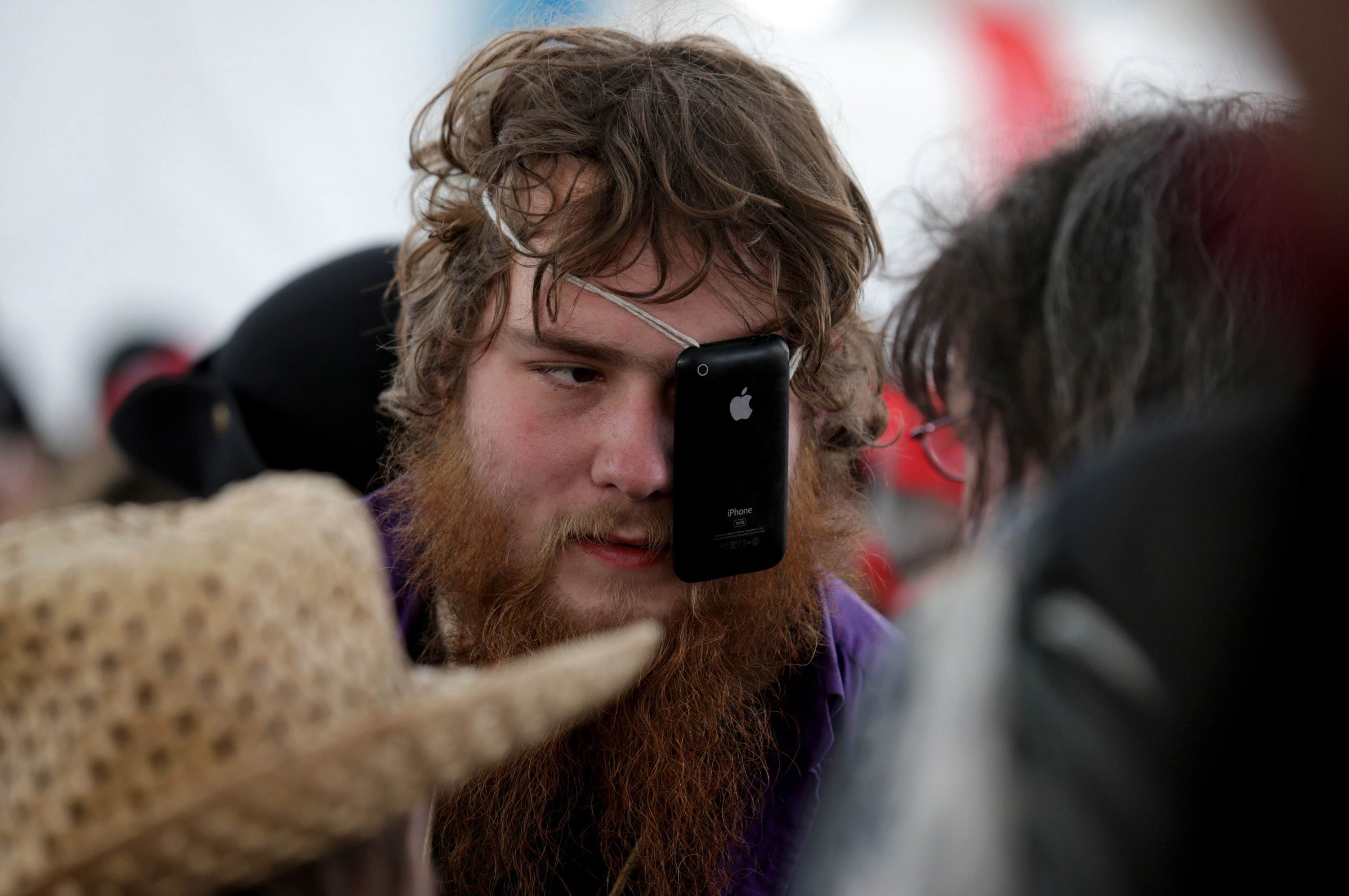 A man uses a iPhone as a eye patch