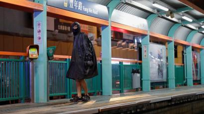 Proestor in HK subway with face masked by raincoat.