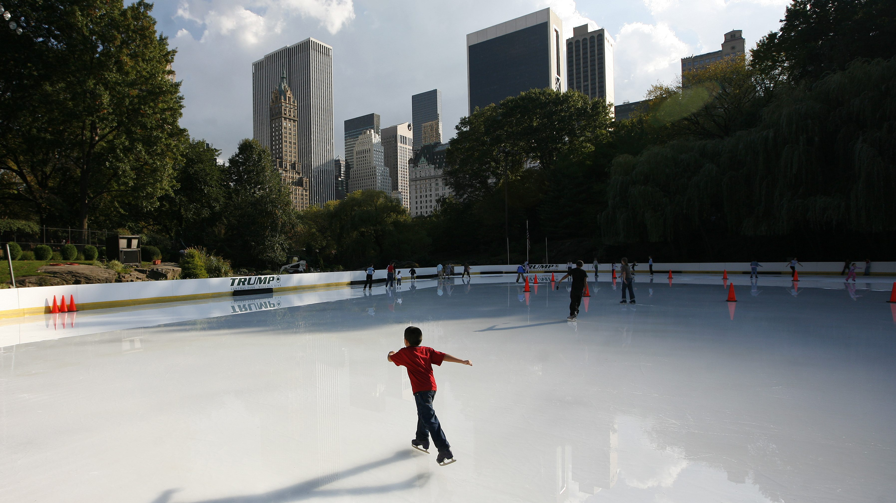 People skate on the Wollman ice rink in Central Park, which opened for the season today to temperatures in the mid 70's, in New York