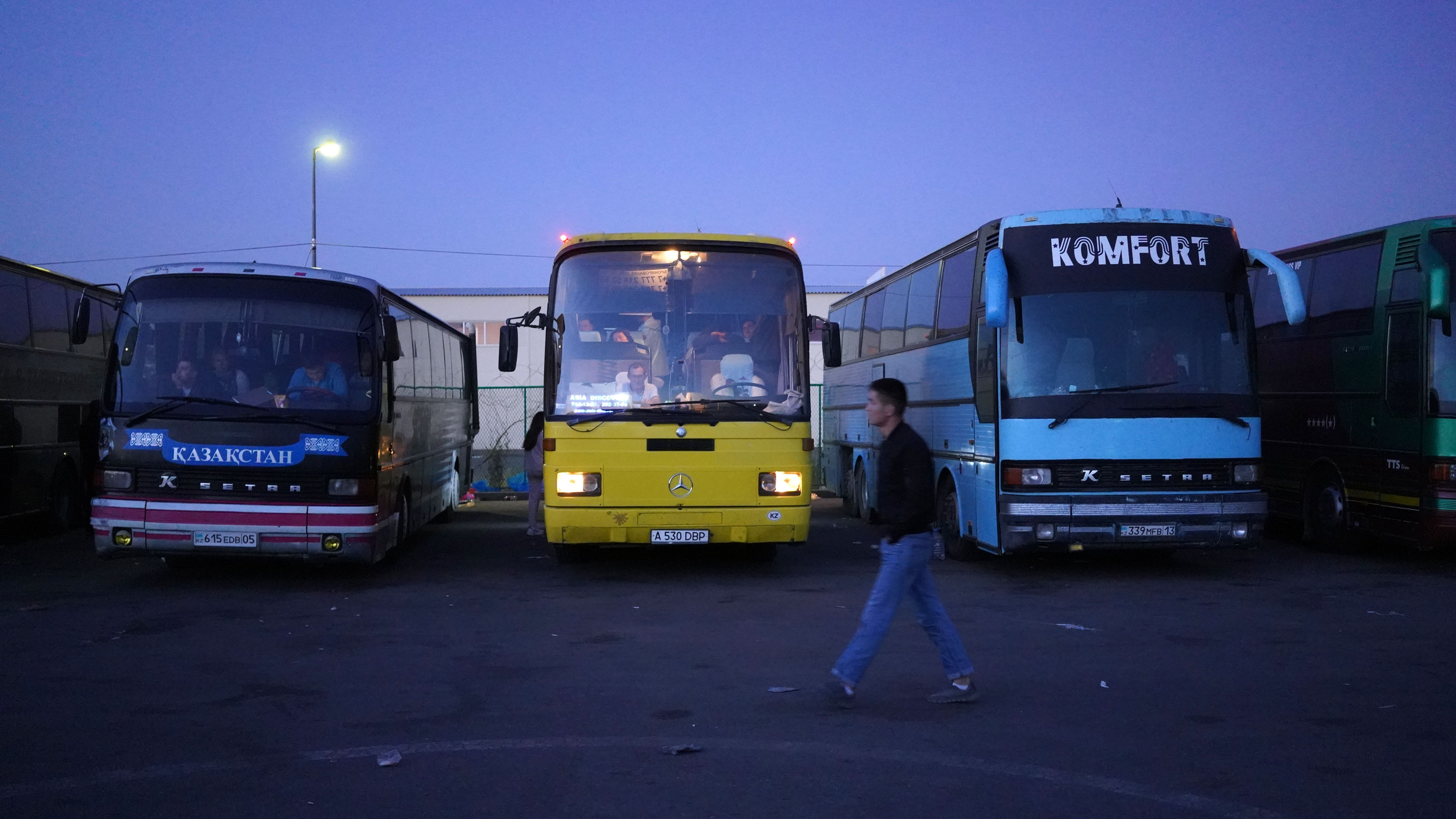 The bus passengers start to wake up as dawn falls at the parking lot outside the customs checkpoint at Khorgos.