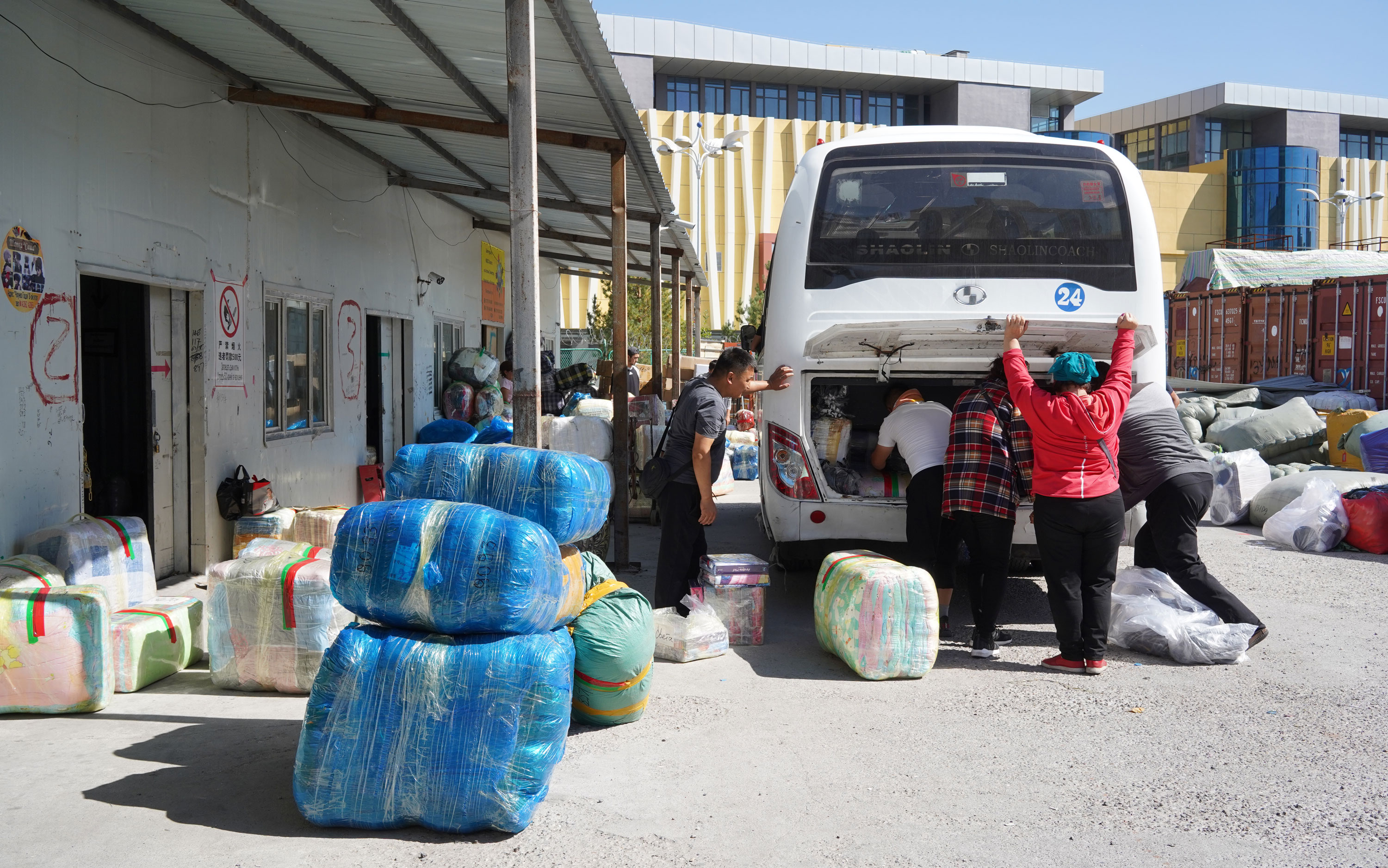 The shoppers stuff their purchases onto the shuttle bus, preparing to leave Khorgos ICBC.
