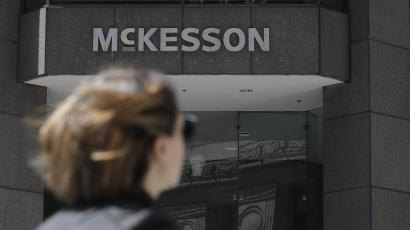 A pedestrian passes a McKesson sign on an office building.