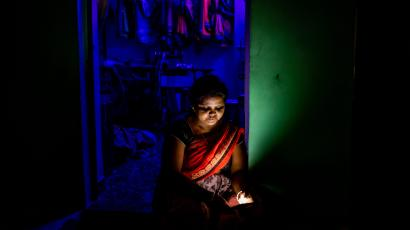 Sweety Devangan, a 42-year-old tailor, checks her phone during a power outage near a power station in Korba, Chhattisgarh, India.