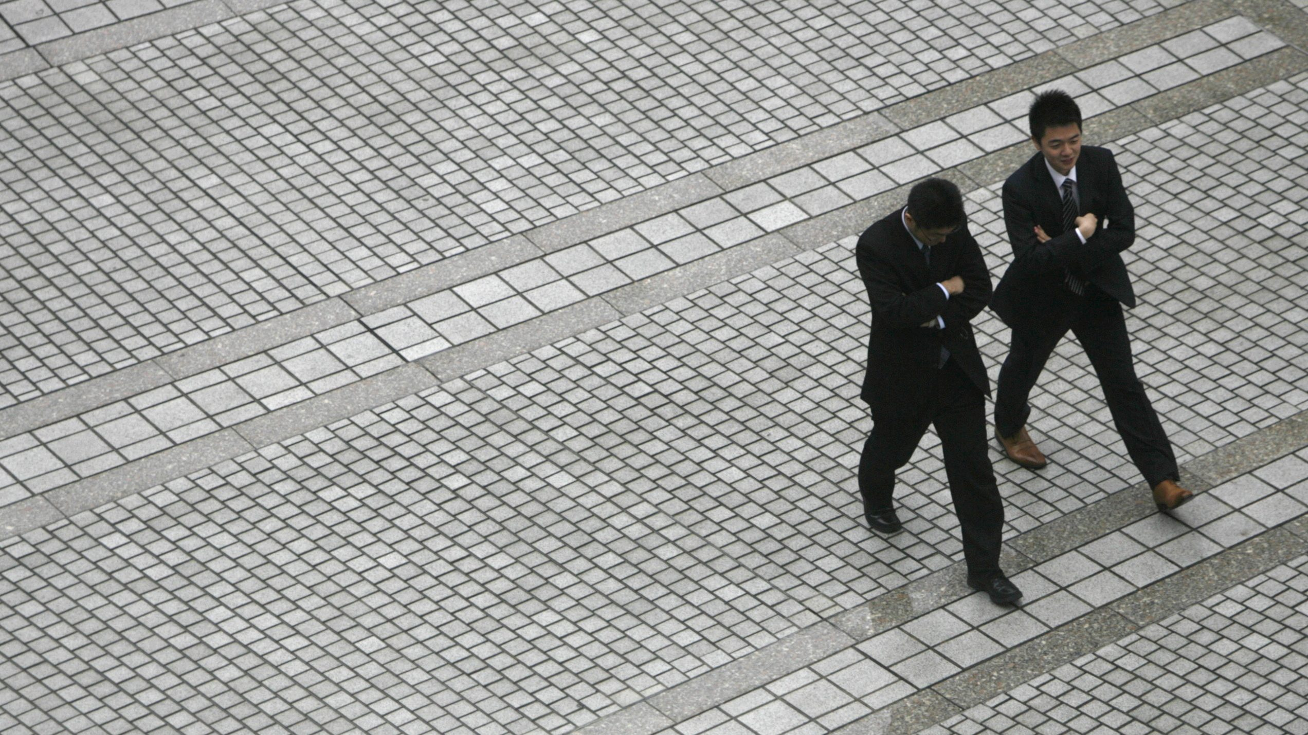 Businessmen walk though a square in Tokyo