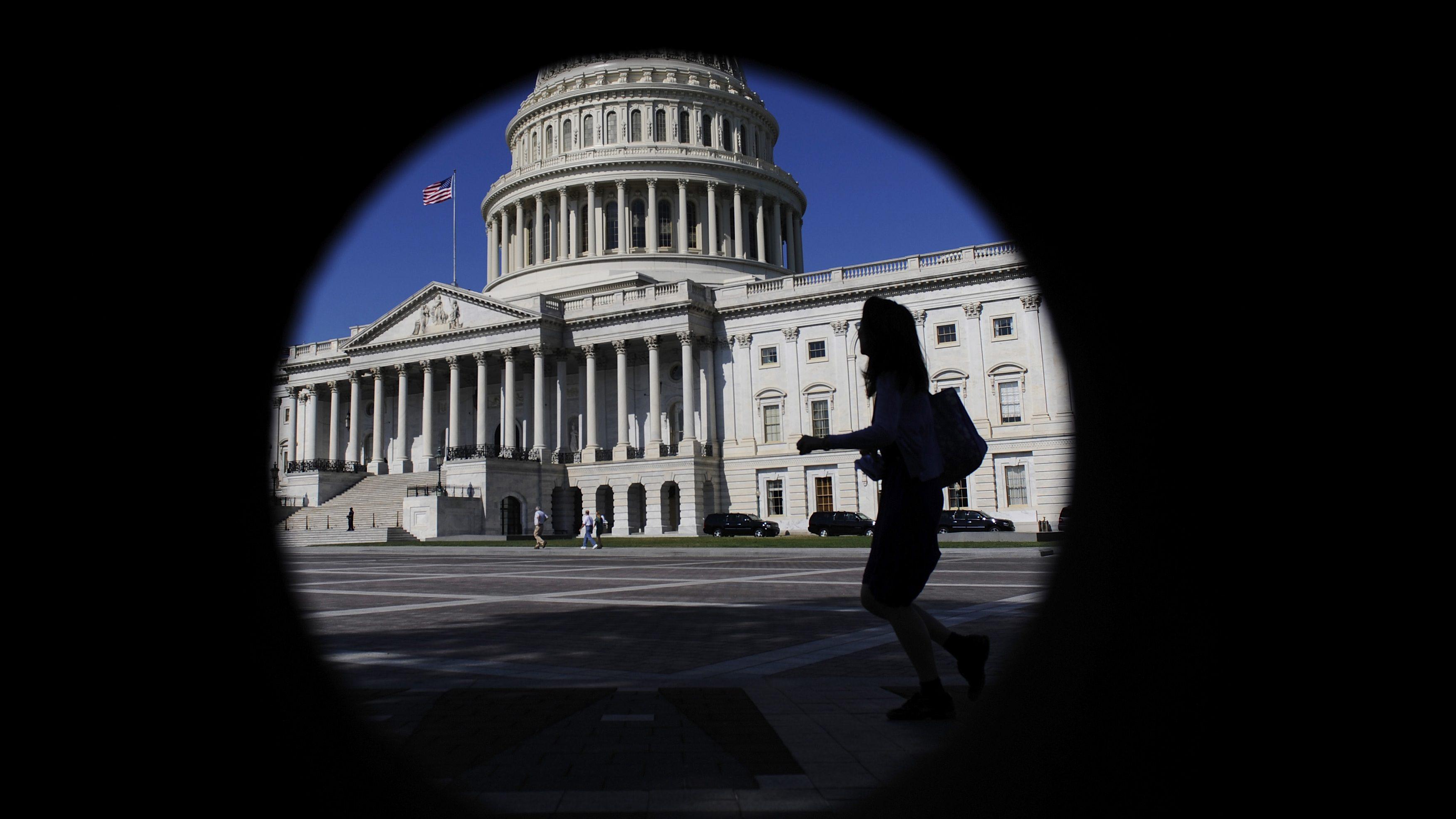 A woman walks past the US Capitol Building