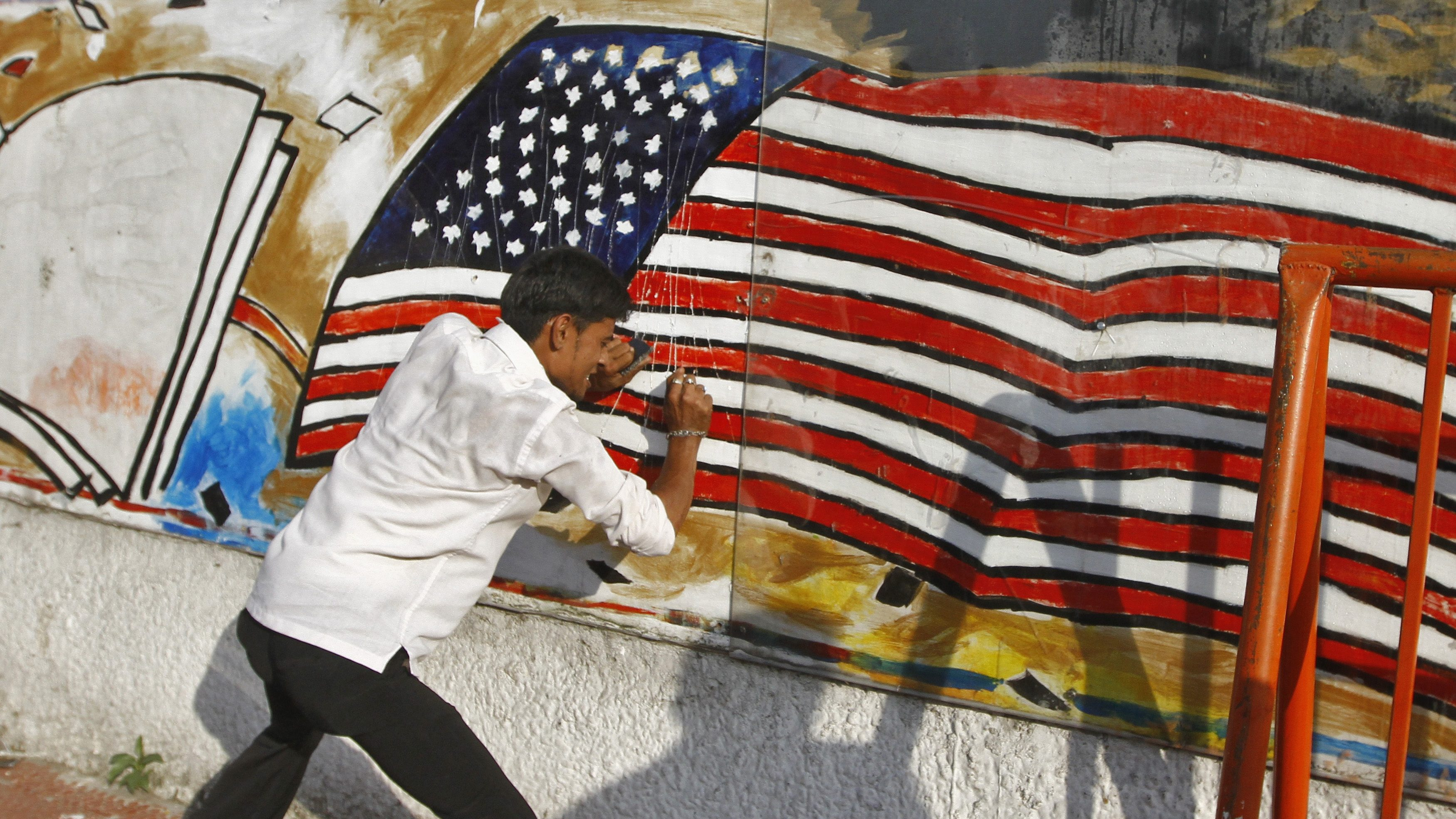 A Muslim protester defaces a mural featuring a U.S. flag on wall of U.S. Consulate-general during a protest against a film they consider blasphemous to Islam, in Chennai