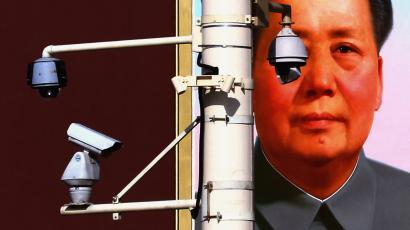 Security cameras attached to pole in front of a portrait of former Chairman Mao at Beijing's Tiananmen Square