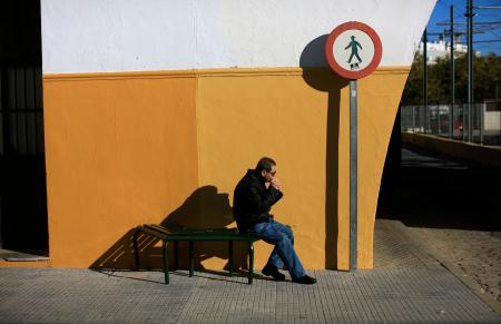 A man sits on a bench as he eats a sandwich at El Prado de San Sebastian coach station in the Andalusian capital of Seville