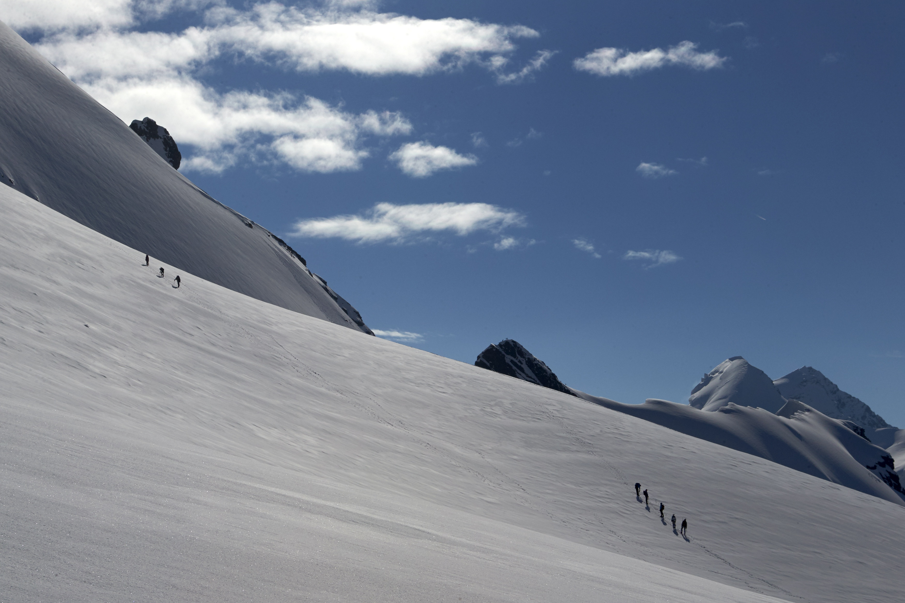 Mountain climbers tied together make their way up a steep, snowy peak with a blue sky in the background.