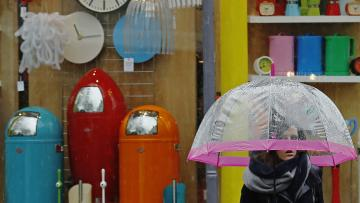 A woman carrying an umbrella passes a shop selling brightly coloured household items in Brighton southern England January 8, 2015
