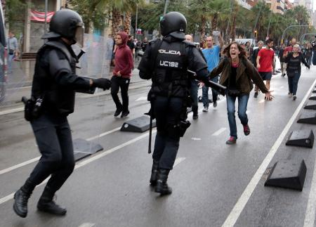 A woman yells at riot police near a a polling station for the banned independence referendum in Barcelona, Spain, October 1, 2017.