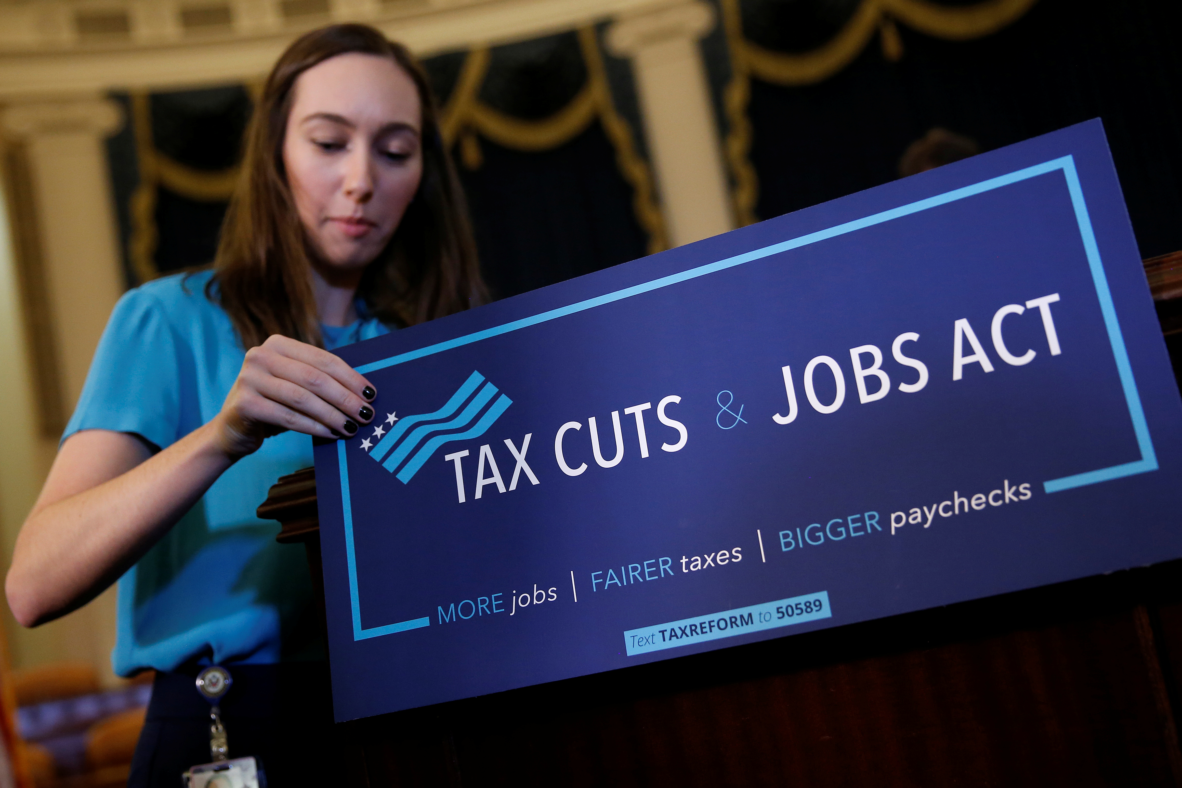 A congressional aide places a placard on a podium for the House Republican's legislation to overhaul the tax code on Capitol Hill in Washington