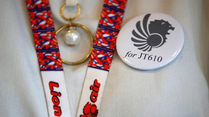 A flight attendant of Lion Air wears a pin commemorating Lion Air flight JT610 as she prepares for a news conference about the recovery process at a hotel in Jakarta, Indonesia, November 5, 2018.