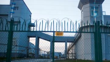 A fence with spikes and barbed wire guards a facility in Xinjiang