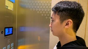 A staff member has his face scanned at an elevator during a demonstration to the media at Alibaba's FlyZoo hotel in China