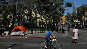 Pedestrians and cyclists pass by tents and tarps erected by homeless people in the skid row area of downtown Los Angeles, California