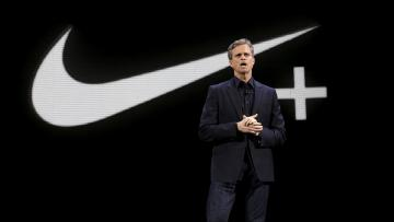 Mark Parker stands against a black background with a Nike swoosh and a plus sign