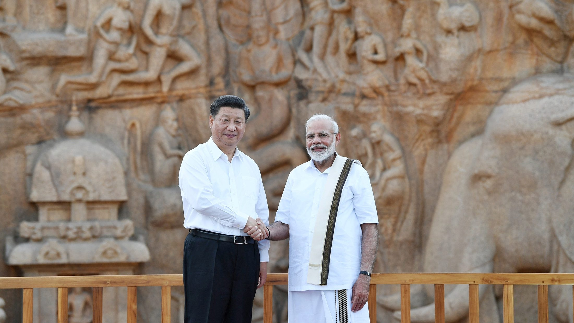 China's President Xi Jinping shakes hand with India's Prime Minister Narendra Modi during their visit to Arjuna's Penance in Mamallapuram