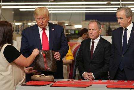 U.S. President Donald Trump holds a purse as he visits the Louis Vuitton Rochambeau Ranch leather workshop in Texas.