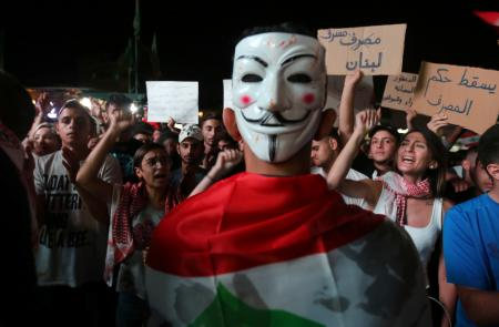 A demonstrator wears a mask during an anti-government protest in the southern city of Nabatiyeh, Lebanon October 22, 2019