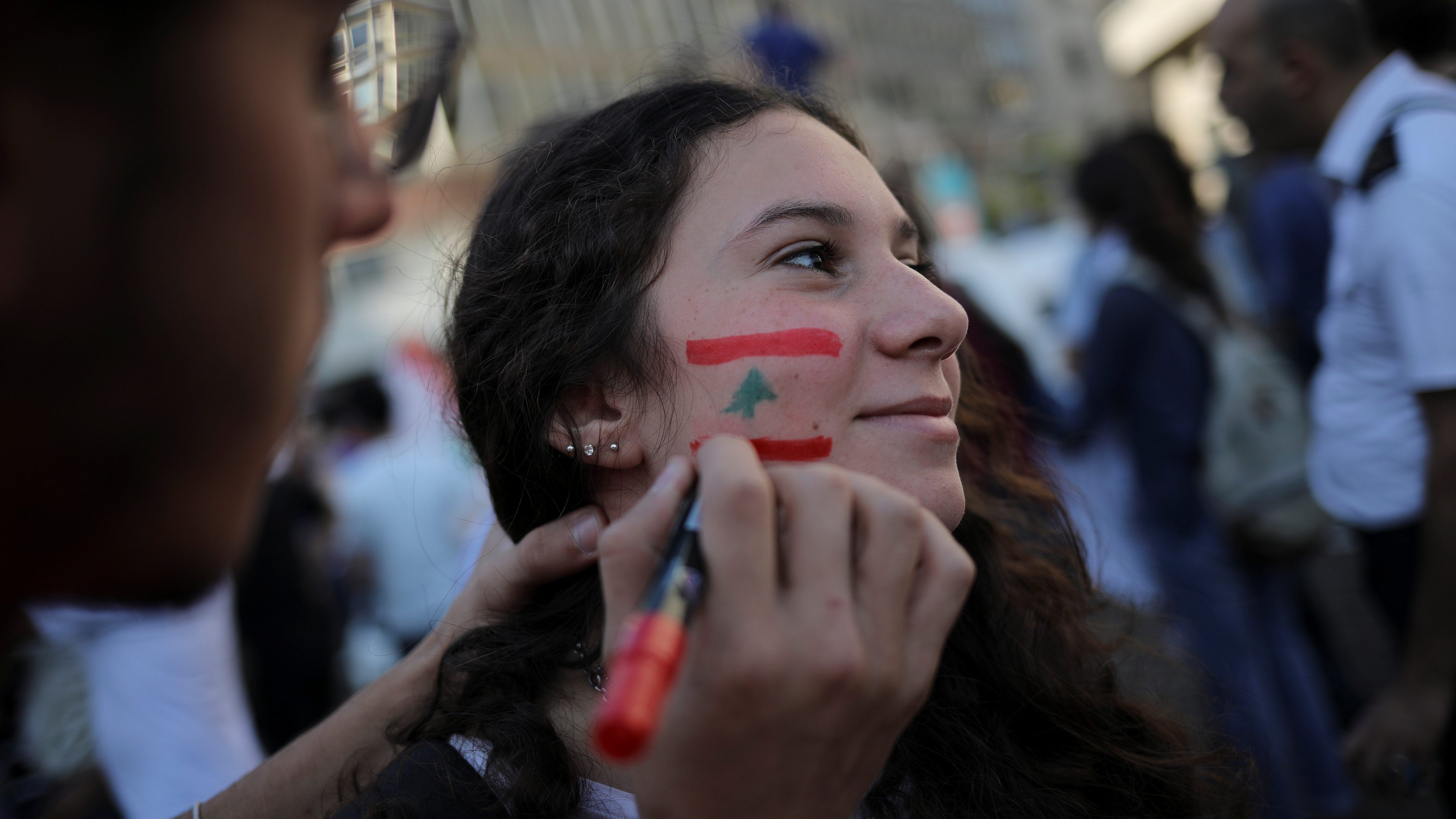 A demonstrator has her face painted in the colours of the Lebanese flag during an anti-government protest in downtown Beirut, Lebanon October 22, 2019. Picture taken October 22, 2019.