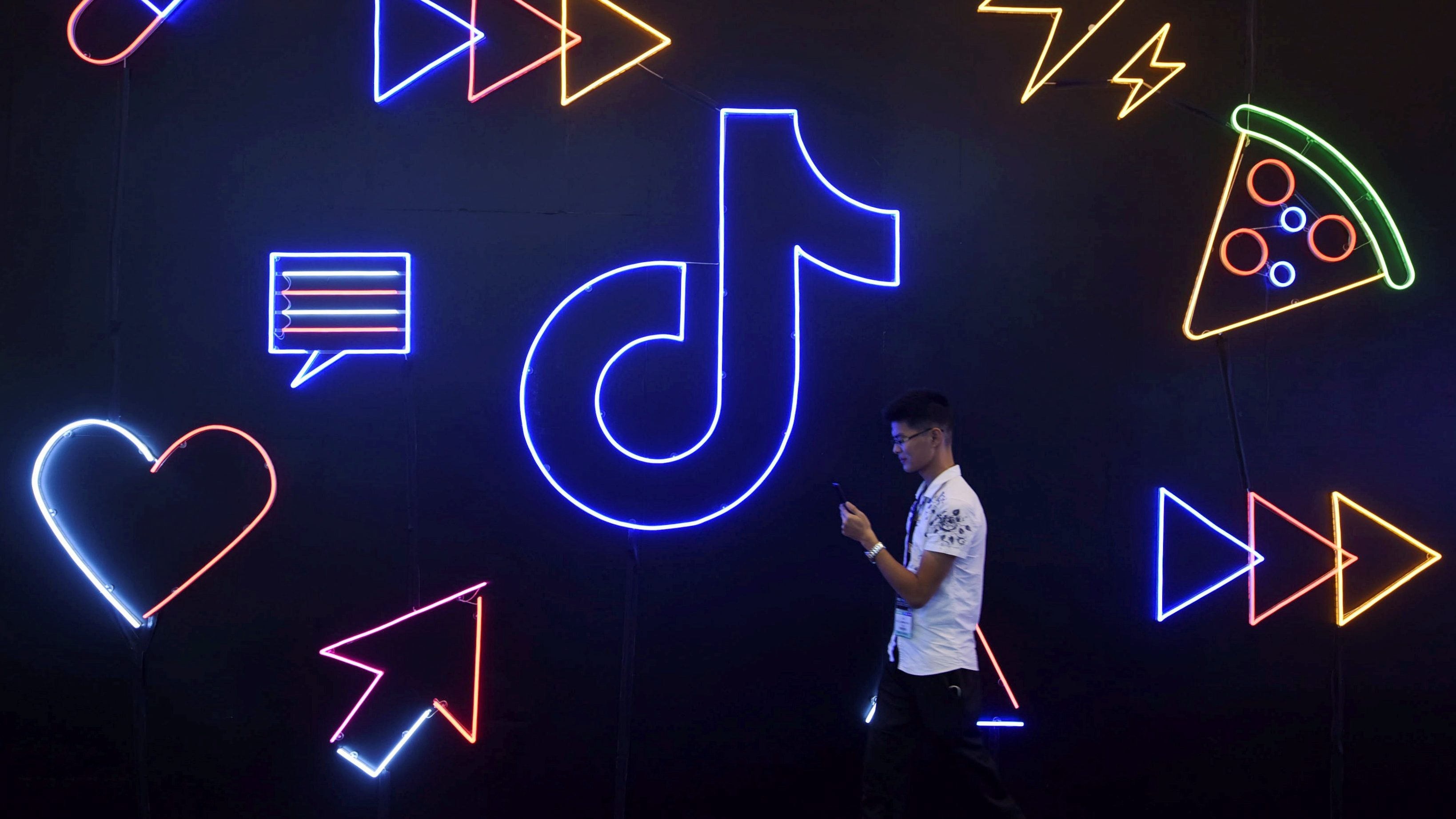 A man holding a phone walks past a sign of Chinese company ByteDance's app TikTok