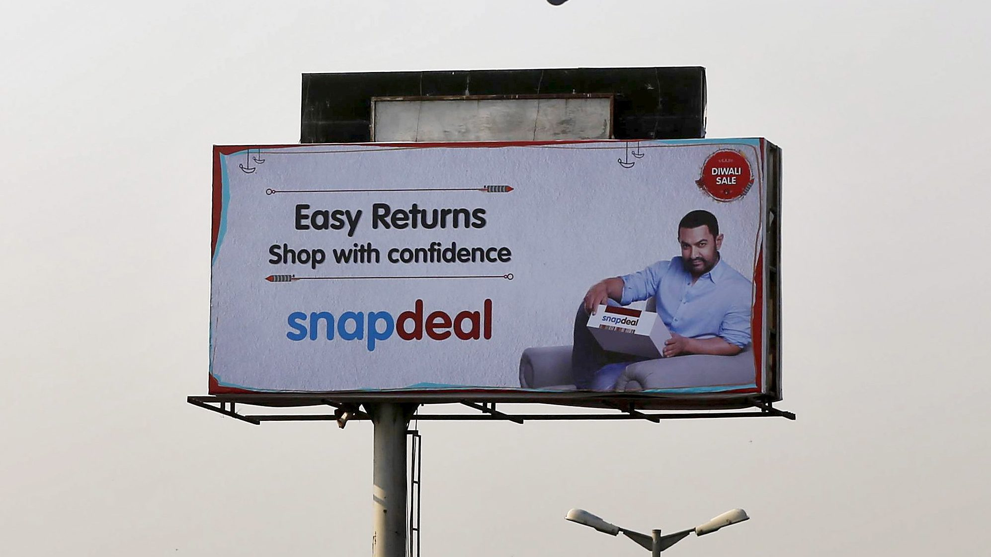 An IndiGo Airlines aircraft flies above an advertisement of Indian online marketplace Snapdeal featuring Bollywood actor Aamir Khan, in Mumbai, India, October 16, 2015. Amazon.com Inc could emerge as the biggest winner from one of India's most important festive - and shopping - seasons, after the e-tailer offered steep discounts, swift delivery and even gold bars to grab market share. The month-long festive season, which began on Monday, culminates in Diwali, or the Festival of Lights, but the first nine days are considered an especially auspicious time to make big purchases. Analysts say e-commerce firms in India could make as much as a quarter of their annual sales during this period, with the global experience, logistics network and deep pockets of Amazon putting it in a good position to grab customers from local market leader Flipkart and smaller firm Snapdeal. REUTERS/Shailesh Andrade - GF10000246866