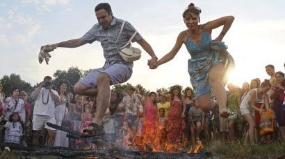 A couple jump over a campfire during a celebration of the traditional Ivana Kupala holiday near Kiev