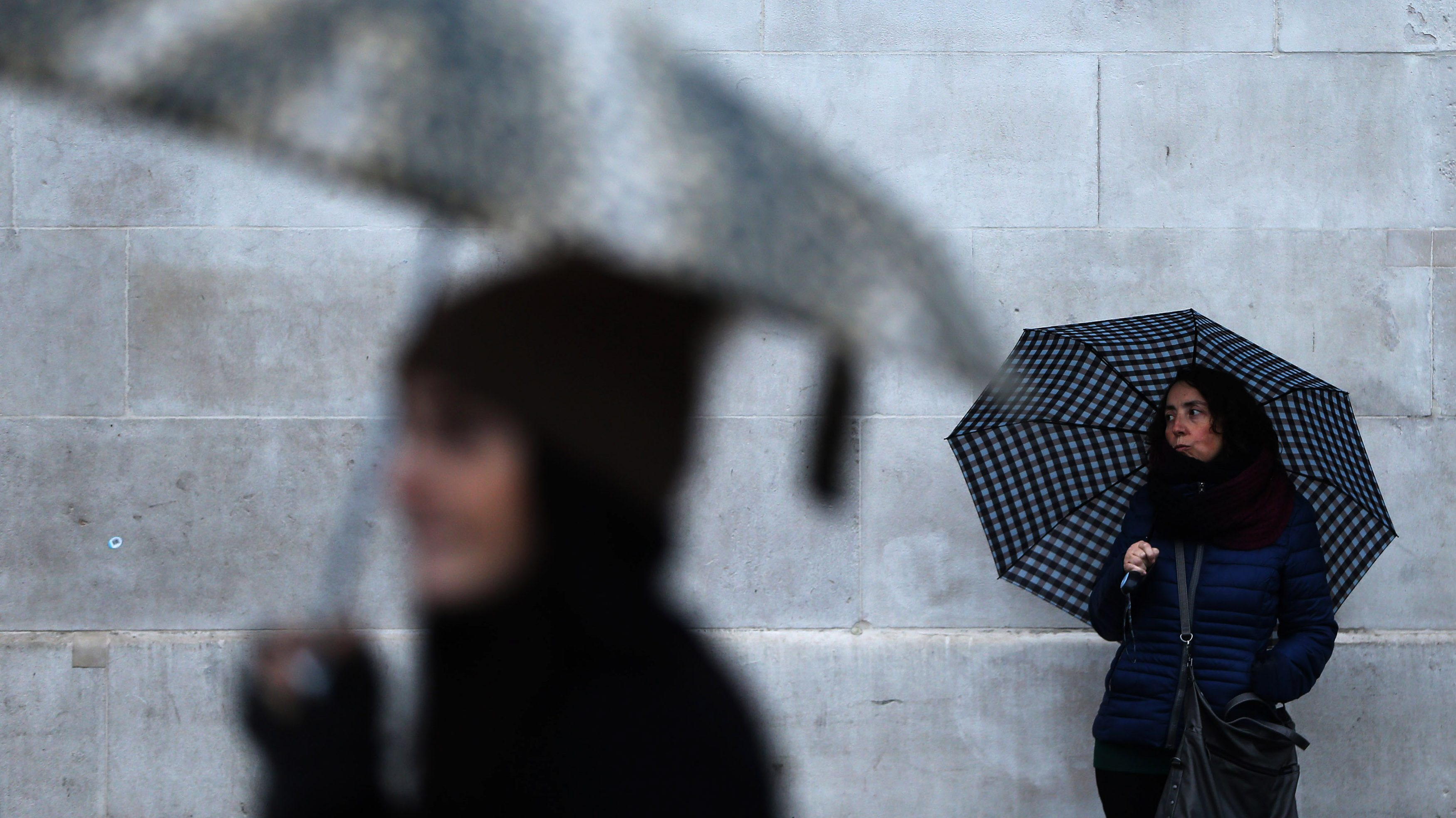 People shelter under umbrellas on a rainy day in central London, Britain