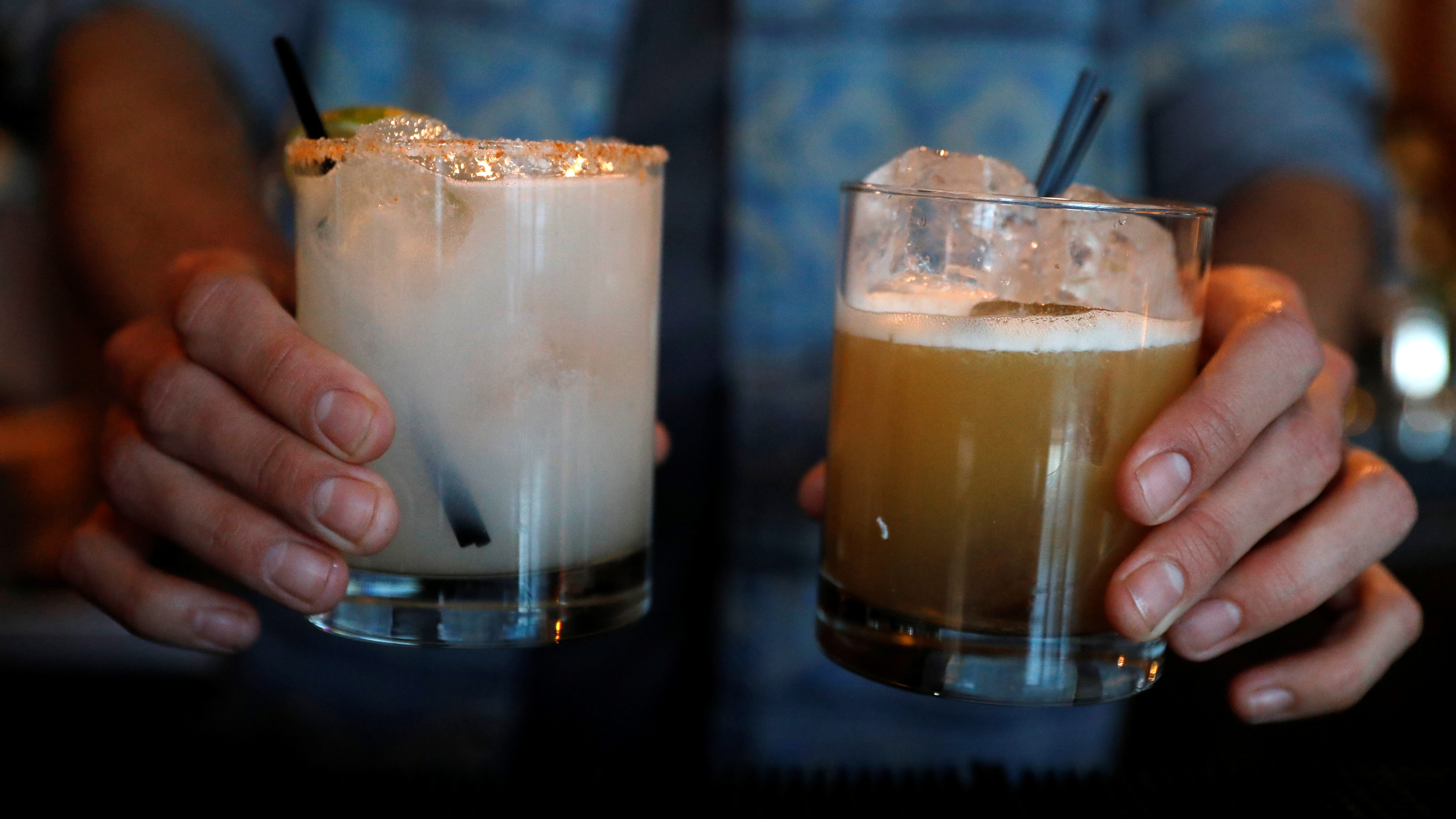 A bartender holds two cocktails, one milky white and the other a light brown.