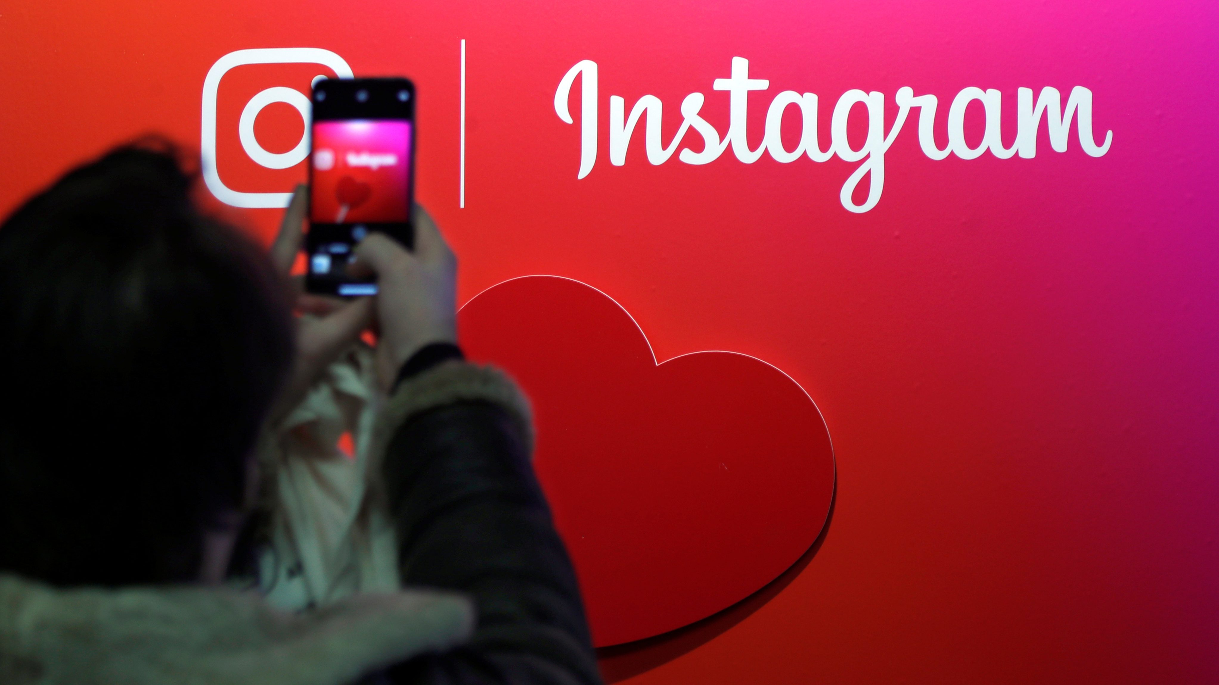 A visitor takes a picture of the Instagram application logo at the Young Entrepreneurs fair in Paris
