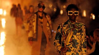 A model walks a runway lined in fire at a Gucci show
