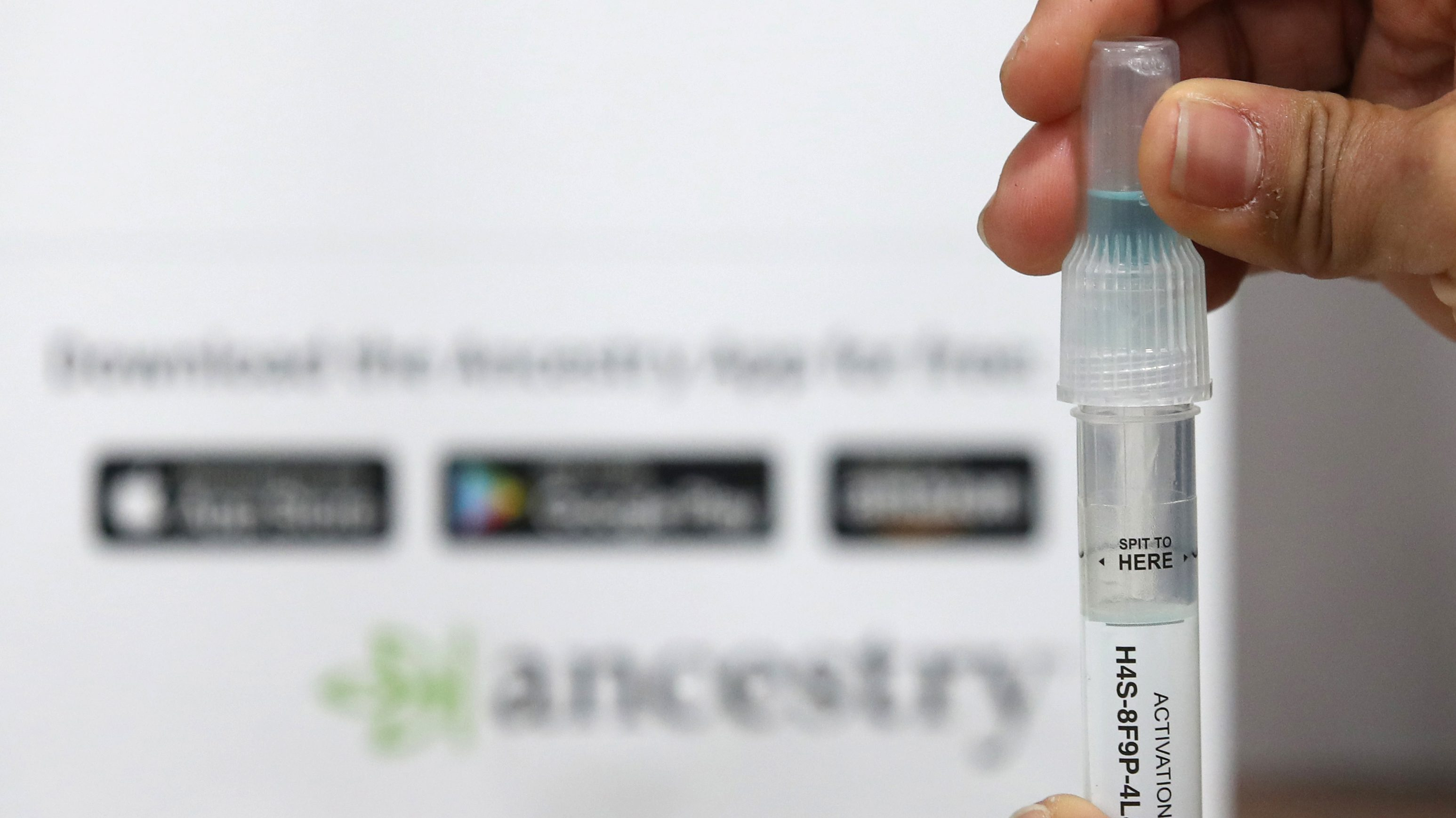 A vial of spit in front of the AncestryDNA logo