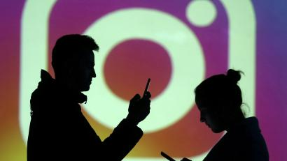 Silhouettes of mobile users are seen next to a screen projection of Instagram logo