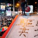 An anti-government protester wearing mask smashes the logo of MTR during a demonstration after government's ban on face masks under emergency law, at Mong Kok, in Hong Kong, China, October 4, 2019.