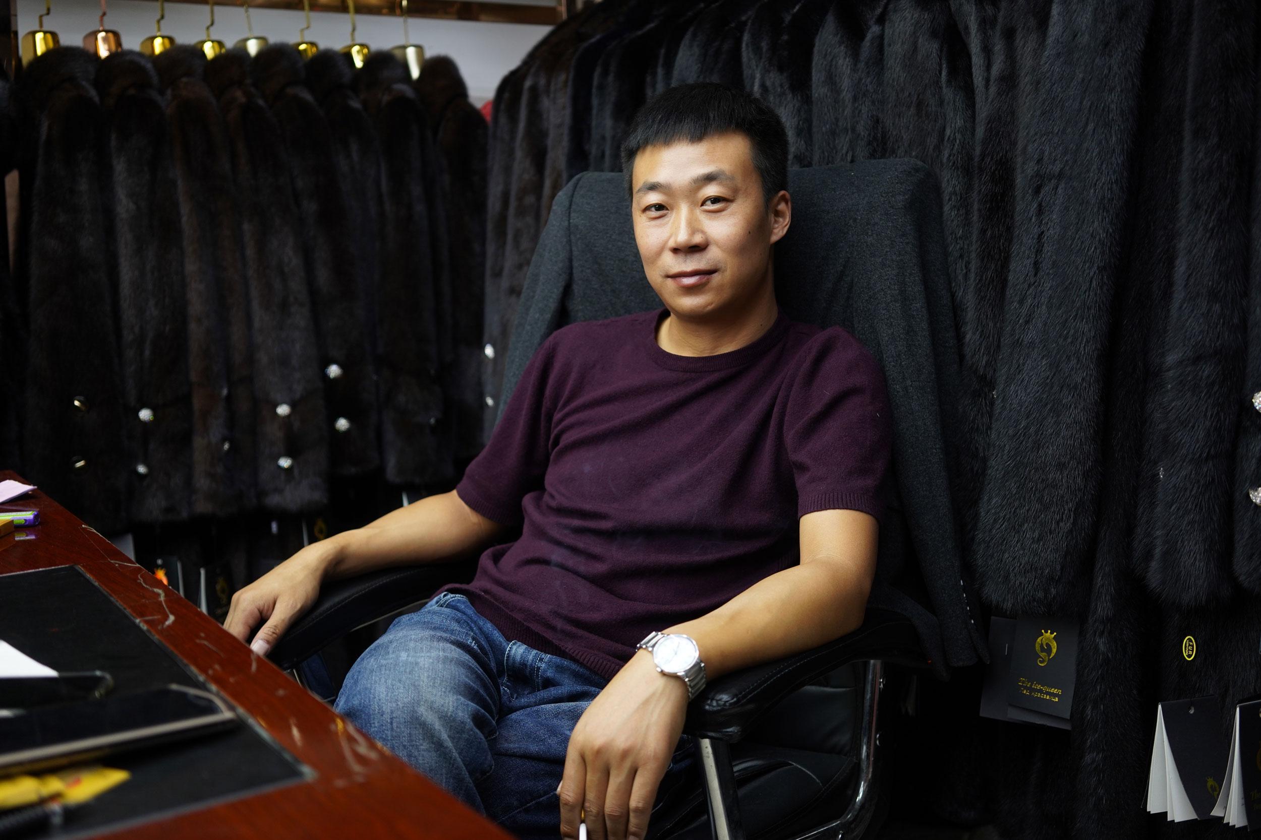 Wenyuan Wang sits at the back of his fur coat store in Khorgos ICBC.