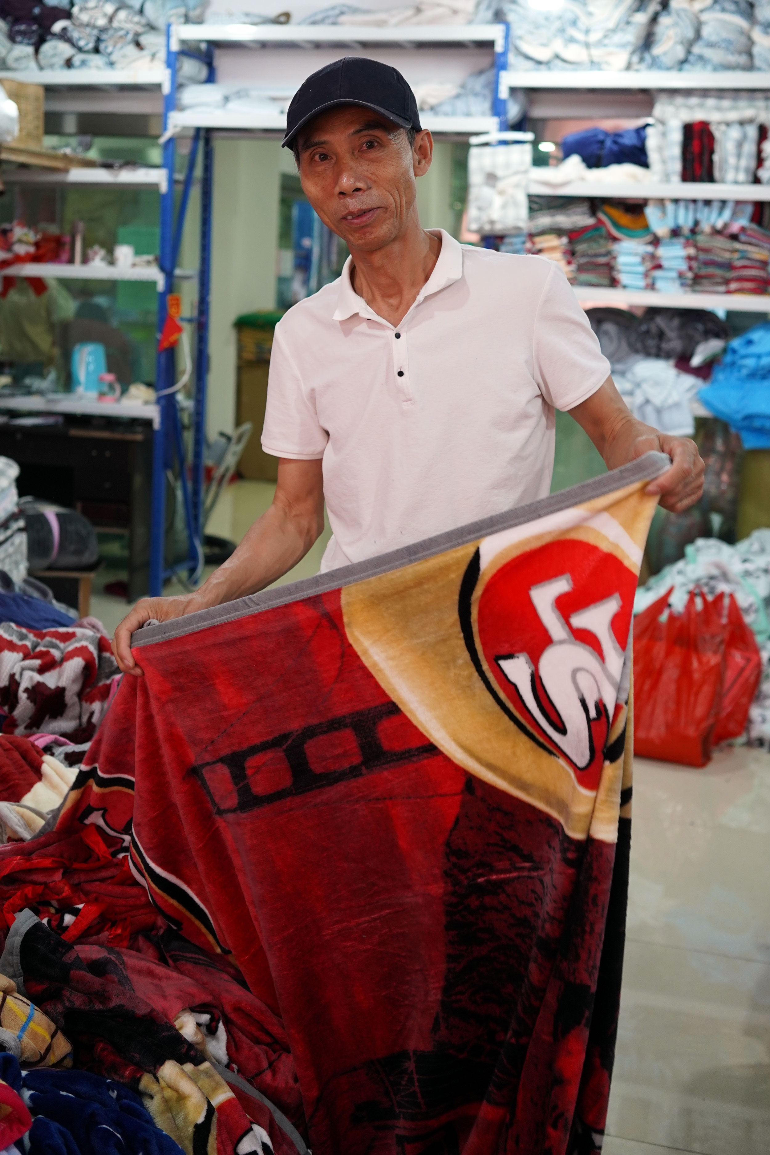 Changhe Zhou folds a blanket at his linen shop in Khorgos ICBC.