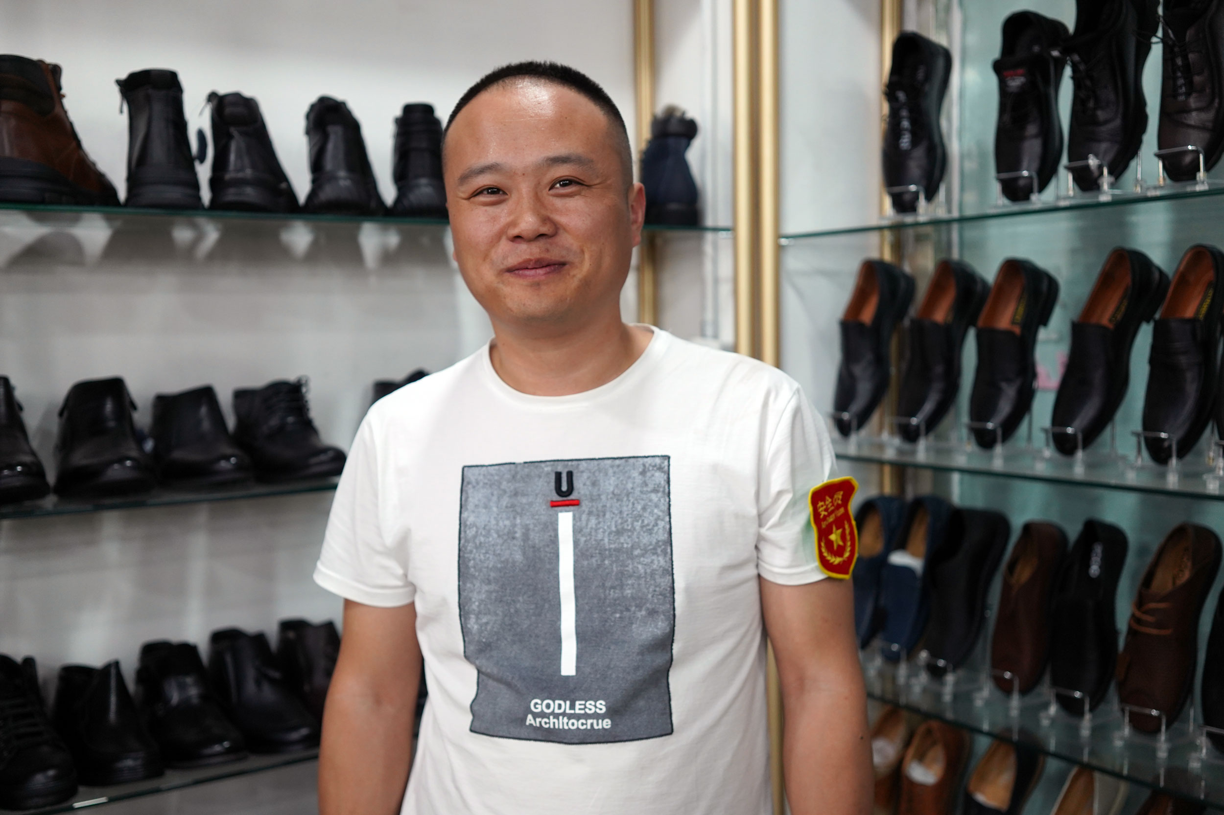 """Xiaopeng Gao stands in front of a shelf of men's shoes at his store in Khorgos ICBC. He wears the badge that says """"security personnel."""""""