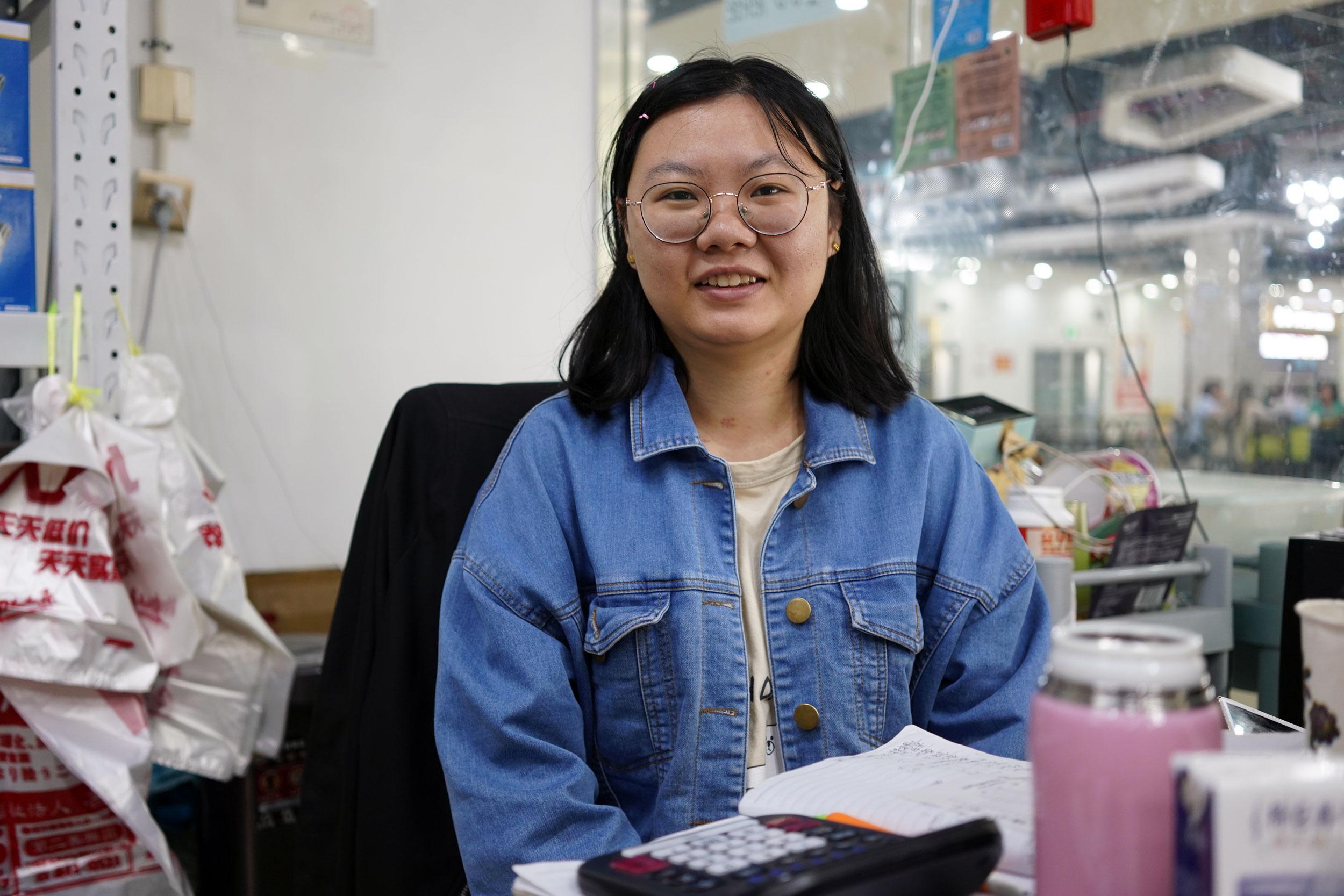 Siyuan Wang, the 27-year-old medical equipment shop owner, sits at her desk at Khorgos ICBC.