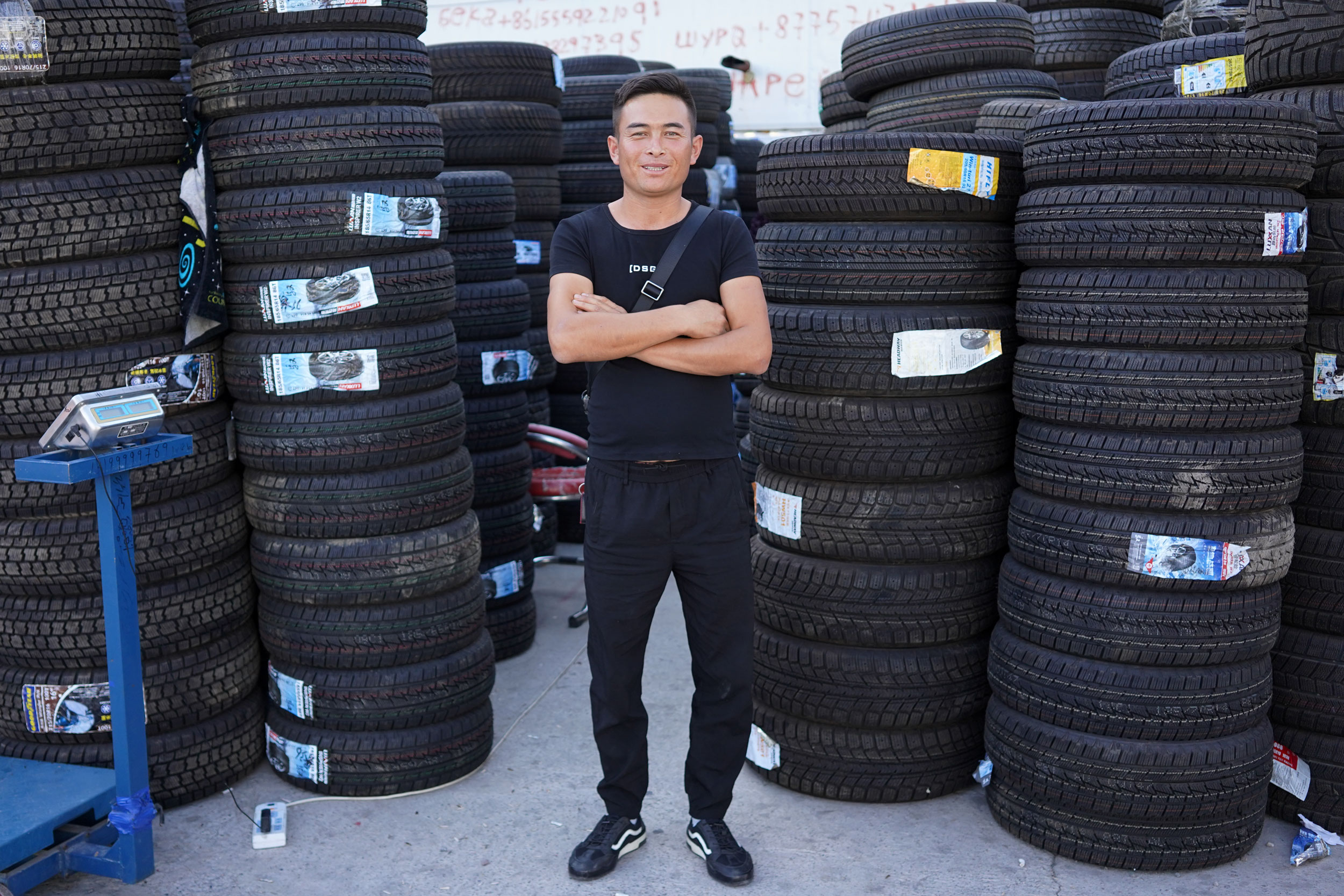 Beka stands in front of his tire store in Khorgos ICBC.