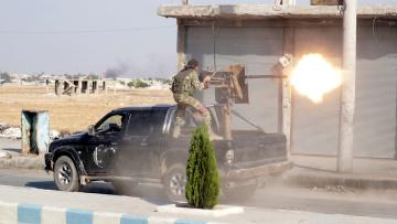 A Turkey-backed Syrian rebel fighter fires a weapon in the town of Tal Abyad