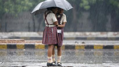 Schoolgirls stand on a road divider as they huddle under an umbrella.