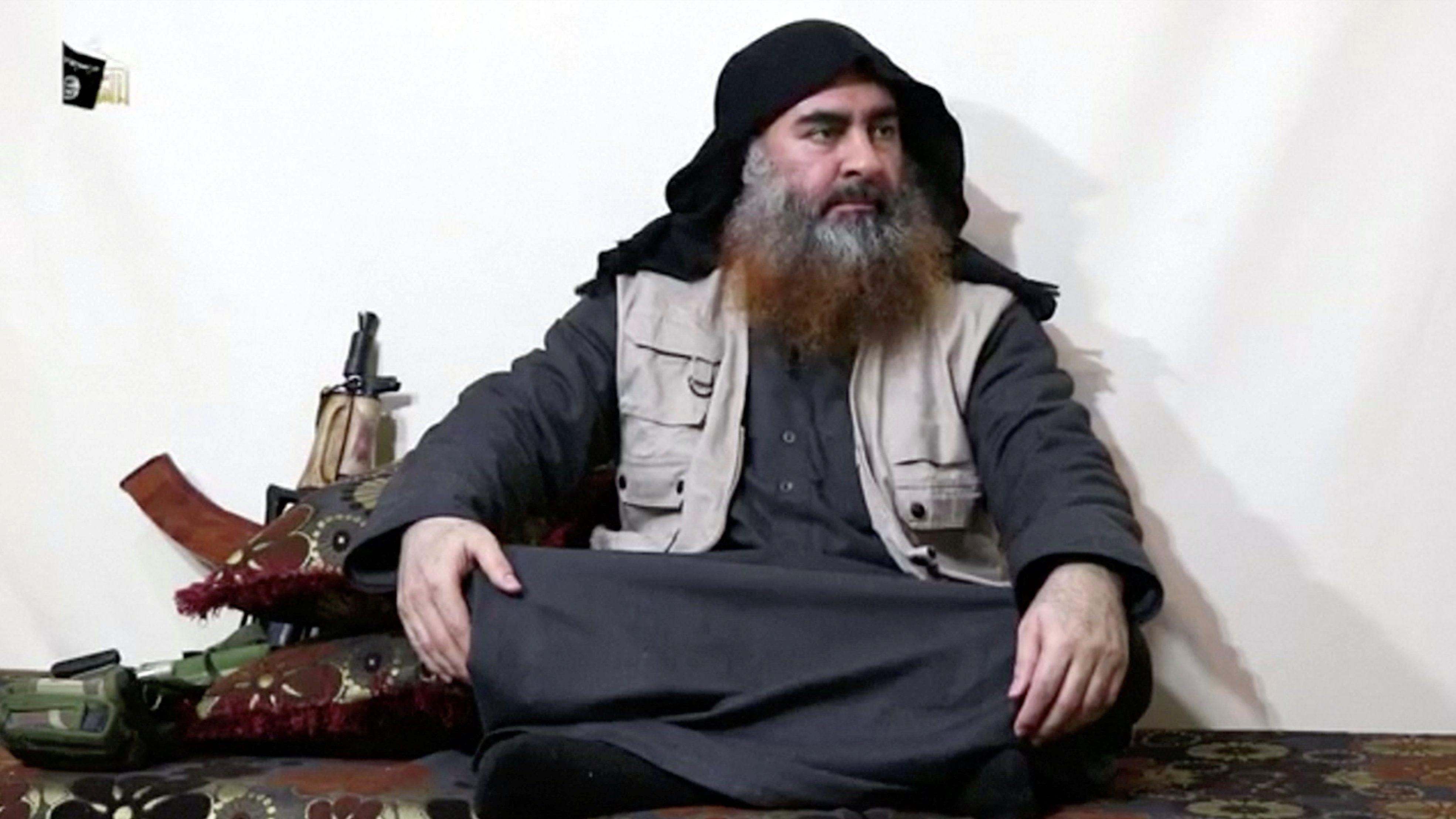 Photo of ISIS leader Abu Bakr al-Baghdadi in a rare appearance. He is sitting crossed legged near a rifle.