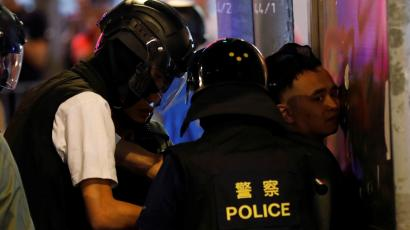 Hong Kong police detain protester.